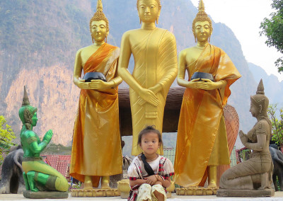 A young girls sitting in front of statues of Indra and Buddha at Wat Sinxay